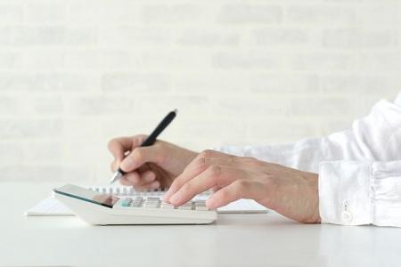電卓をうちながら紙に何か書いている男性
