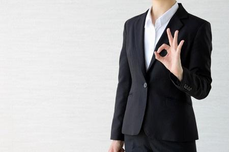 OKサインをするスーツを着た女性