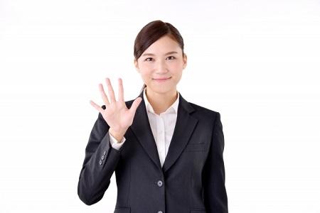 5と手で指し示すスーツを着た女性