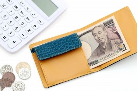 一万円が入った財布と電卓と小銭