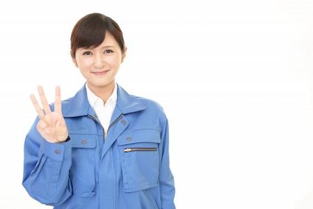 作業服を着た女性が指で3を示している