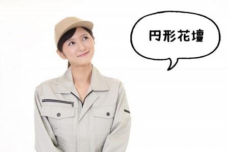 円形花壇と話す作業服の女性