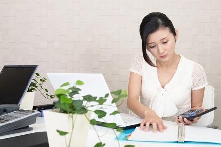 電卓を持ち仕事をするデスクワークの女性