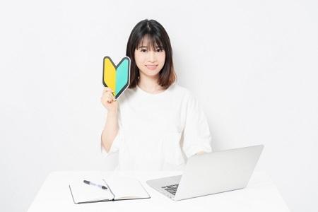 ノートパソコンの前で初心者マークを持った女性